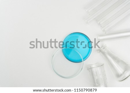 top view of laboratory equipments. A blue liquid watch glass, flask, test tubes and beaker on the white table