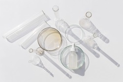 Top view of laboratory glassware and cosmetic glass bottle on grey background. Natural medicine, cosmetic research, bio science, organic skin care products.
