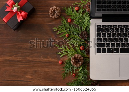 Top view of laptop and Christmas decorations with gift box. Concept of preparation for holiday season campaigns,marketing, shopping, sales and articles etc.