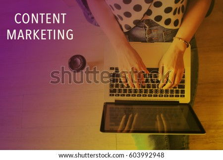 Top view of laptop in girl's hands sitting on a wooden floor with coffee, content marketing word, color transitions style