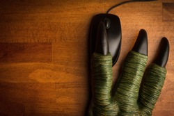 top view of large green toy dragon monster paw with big black claws and three fingers using a computer mouse on wooden desk