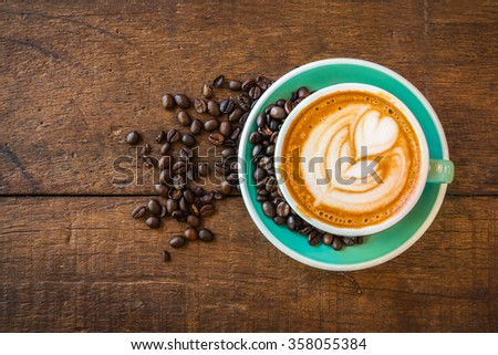 Top view of Latte hot coffee (or cappuccino) in a green cup with latte art and roasted coffee beans on wooden table background #358055384