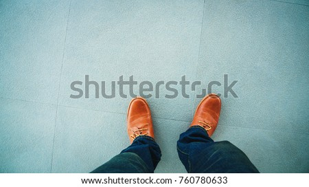Top view of leather shoes standing on stone floor tiles backgrounds