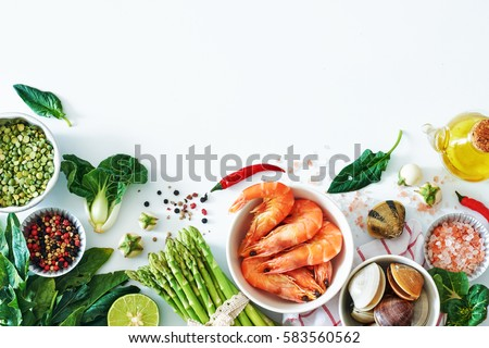 Top view of light dinner ingredients over white background with a copy space. Cooked prawns, clamps, asparagus, spinach, baby eggplant, brown rice, salt and pepper.