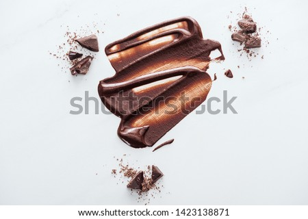 Top view of liquid chocolate with pieces of chocolate and cocoa powder