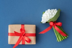 Top view of little bouquet of gentle snowdrops with red ribbon and wrapped giftbox on blue background. Copyspace for text. Greetings concept. Layout for postcard.