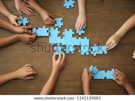 Top view of little children playing puzzle together at table, focus on hands. Unity concept #1142139083