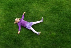 Top view of little girl lying on grass