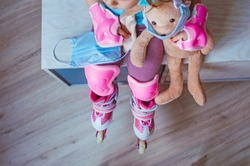 Top view of little girl wearing pink roller skates holding her face mask and bunny soft toy sitting indoor. Selective focus on the mask. Social distance stay at home during Covid-19 Pandemic concept.