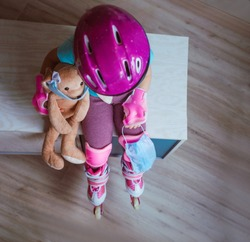 Top view of little girl wearing pink roller skates, knee pads, wristbands and helmet holding her face mask and rabbit soft toy in the mask. Social distance stay at home during Covid-19 Pandemic.