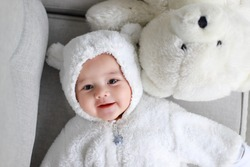 Top view of little infant baby boy wearing teddy bear costume lying next to white polar bear. Happy Asian-German kid 4-5 months old