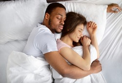 Top view of loving interracial couple sleeping in bed, hugging each other. Overhead shot of black guy embracing his girlfriend while napping. Diverse love and relationships