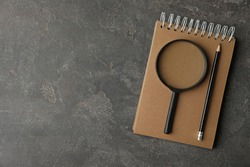 Top view of magnifier glass, empty notebook and pencil on grey stone background, space for text. Find keywords concept
