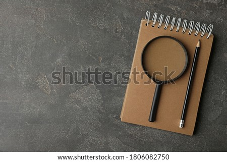 Top view of magnifier glass, empty notebook and pencil on grey stone background, space for text. Find keywords concept Foto stock ©
