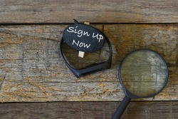 Top view of magnifying glass, watch and wooden tag written with text SIGN UP NOW over wooden background. Business concept.