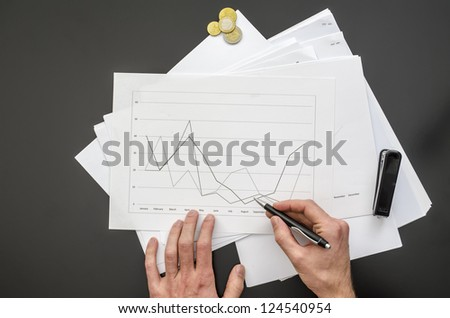 Top view of male hand holding a pen over a business document.