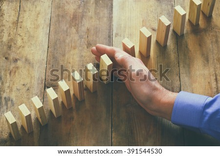 top view of male hand placing wooden block on a tower. planing and strategy concept. vintage filtered