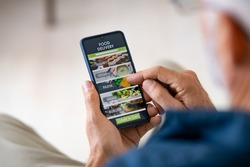 Top view of man hands holding smartphone while order food delivery at home. Back view of mature man using food delivery app with mobile phone to order lunch.