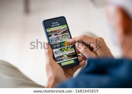 Top view of man hands holding smartphone while order food delivery at home. Back view of mature man using food delivery app with mobile phone to order lunch.  Stockfoto ©