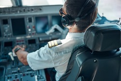 Top view of man in aviation uniform and earphones sitting at control and switching rudder while taking off
