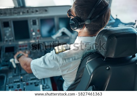 Top view of man in aviation uniform and earphones sitting at control and switching rudder while taking off Сток-фото ©