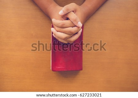 Top view of man praying on holy bible in the morning.teenager boy hand with Bible praying,Hands folded in prayer on a Holy Bible in church concept for faith, spirituality and religion