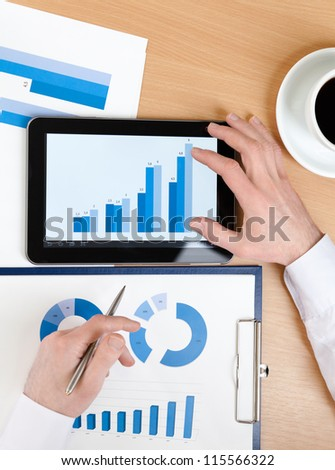 Top view of manager working on the tablet with diagrams. Close up of hands and graphs