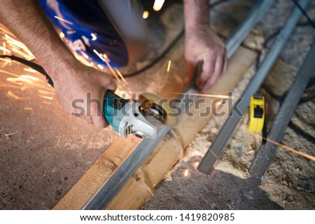 Top view of manual worker cutting steel with grinder industrial machine. Sparks flying.