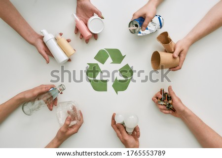 Top view of many hands holding different waste, garbage types with recycling sign made of paper in the center over white background. Sorting, recycling waste concept. Horizontal shot. Top view ストックフォト ©