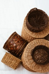 Top view of many natural empty wicker straw cane osier baskets at white background, storage and household concept