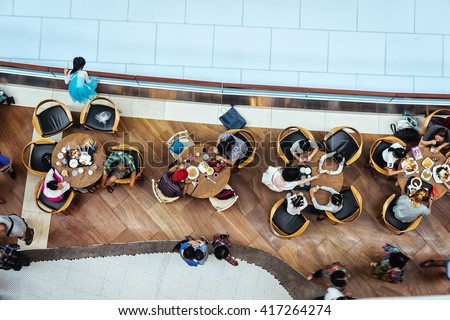 Top view of many people sitting in food court cafe eating lunch near artificial ice rink. City cafe. People having lunch at city cafe. People eating business lunch during work day. Aerial cafe lunch.