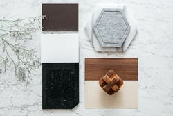 Top view of Material Sample Selections including Granite tile, Marble tile, Acoustic tile, Walnut and Ash Wood Laminate with Plant on marble top table.