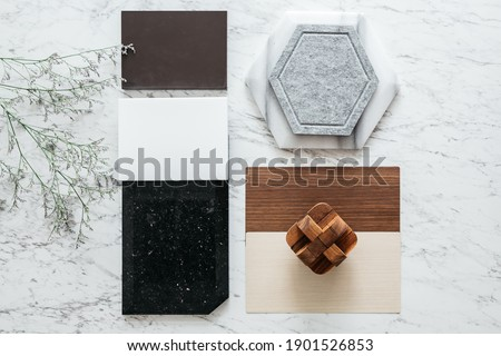 Top view of Material Sample Selections including Granite tile, Marble tile, Acoustic tile, Walnut and Ash Wood Laminate with Plant on marble top table. Foto stock ©