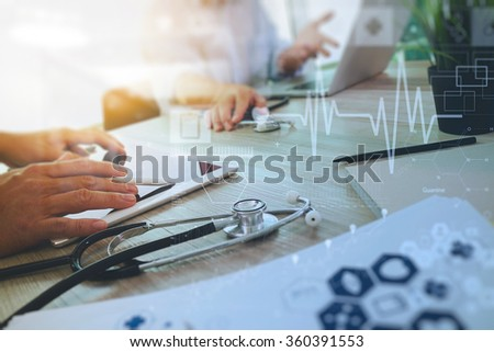 top view of Medicine doctor hand working with modern computer and digital pro tablet with diagram with his team on wooden desk as medical concept