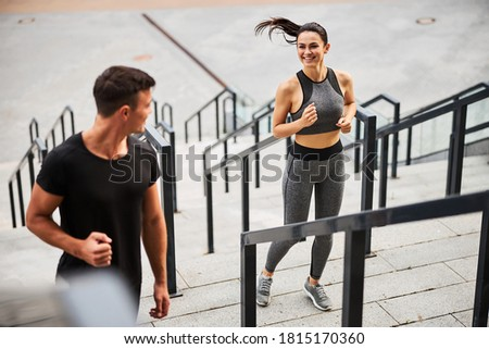 Top view of merry athletic male and female in sportwear running upstairs in city centre Foto stock ©