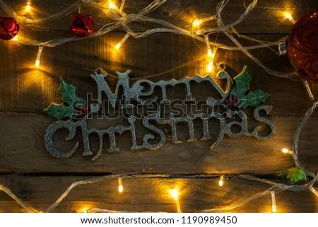 Top view of Merry Christmas text framed by Christmas lights on the wooden table - Shutterstock ID 1190989450