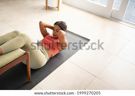 Top view of mid adult fit woman doing press on a mat while keeping legs on chair at home. African american woman practicing crunches at home. High angle view of healthy mixed race girl doing abs. Foto stock ©