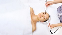 Top view of middle aged woman receiving electrical stimulation facial skin care spa procedure. Micro-current lift face. Beauty spa procedure. Copy space for you text