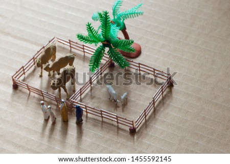 Top view of miniature toy Arab man and wife in abaya buys camel and sheep from a kid on a farm concept. #1455592145