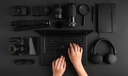 Top view of minimal photographers desk. Female hands working on laptop. Black photography gear flat lay.