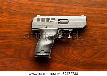 Top view of 9 mm handgun against wooden surface