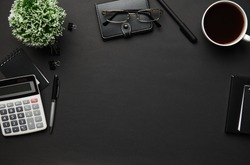 Top view of modern black office desk with calc, notebook, pen and a lot of things. Flat lay table layout. Copy space for text.