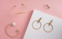 Top view of modern golden girl accessories on pink and white background