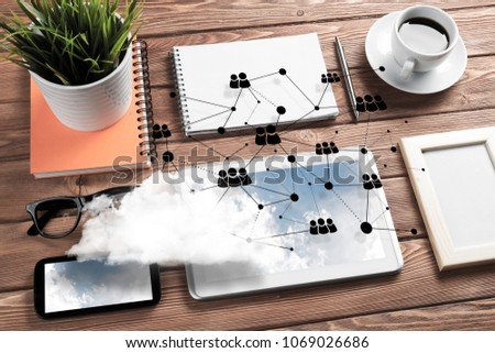 Top view of modern workplace with office stuff, social network connections and clouds above as symbol of still office life. Mixed media. #1069026686
