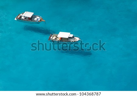 Top view of motorboats in blue, transparent waters of shipwreck bay, Zakynthos