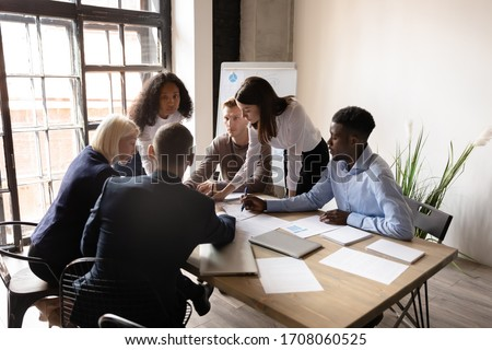 Top view of multicultural colleagues gather at desk in office brainstorm consider paperwork together, diverse employees discuss financial business project ideas at briefing, cooperation concept