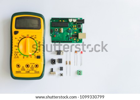 Top view of Multimeter and electronics component such as resistor, ICs, capacitor, switch, relay and connector on white background.