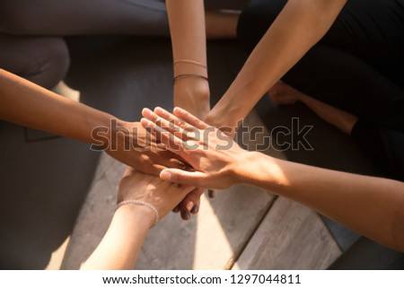 Top view of multiracial women sit in circle on training put hands in stack showing mutual support and unity, female athletes involved in teambuilding activity, motivated for shared goal at workout