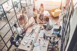 Top view of multiracial young creative people in modern office. Group of young business people are working together with laptop, tablet, smart phone, notebook. Successful hipster team in coworking.