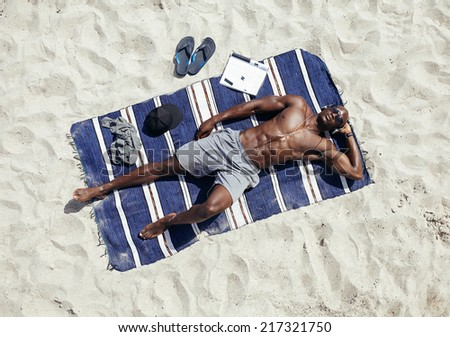Top view of muscular young man sunbathing on beach. African guy wearing sunglasses and listening to music on headphones lying on a beach mat